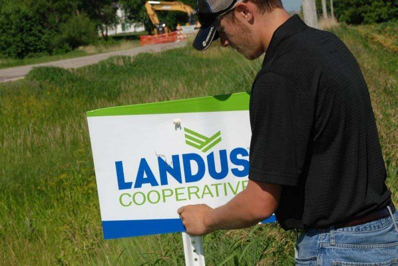 Landus Cooperative Intern putting up field signs